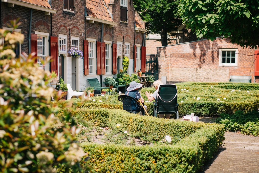 Two elderly ladies chat outside in a lush garden.