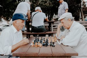 Two older men play a game of chess at an outdoor table.