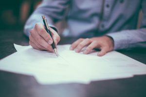 A person in a blue Oxford shirt signs a document.