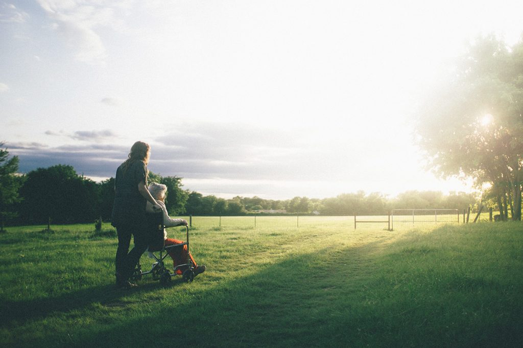 A caregiver stands in a grassy field with her elderly client as they watch the sunset together.
