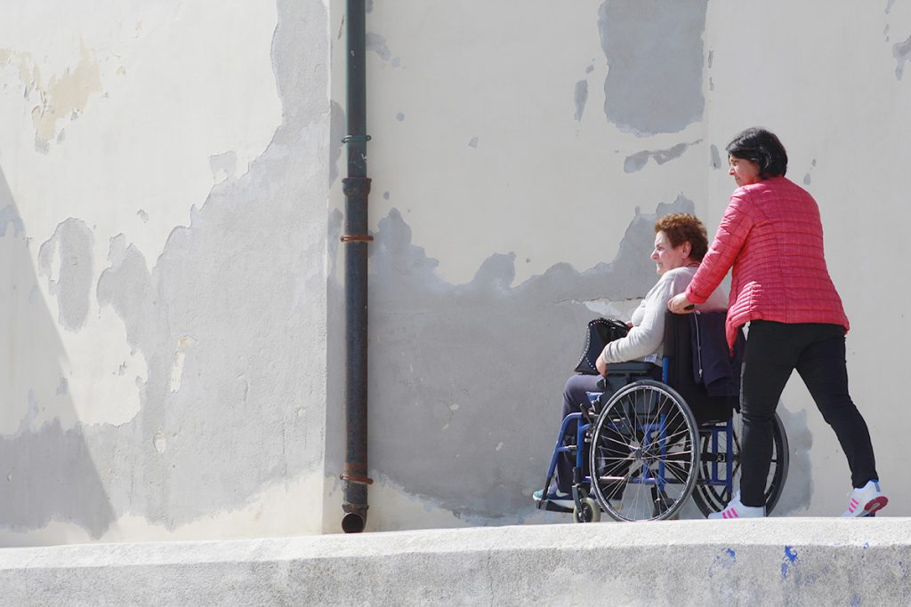 A caregiver in a red jacket pushes an older woman in a wheelchair down a concrete ramp.