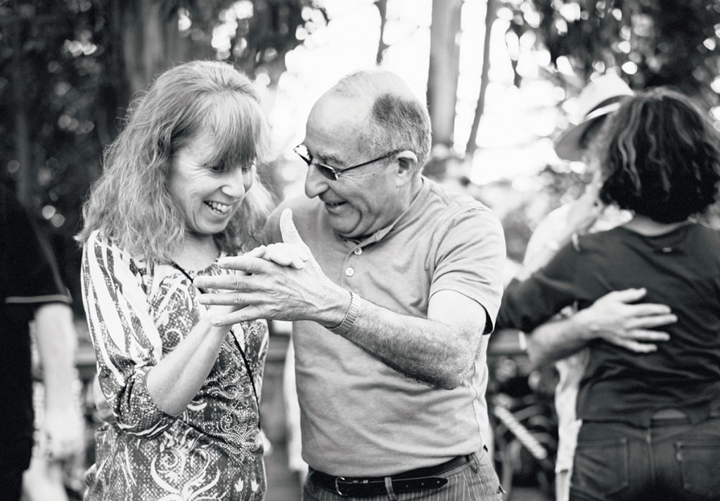 An older woman and man hold hands while dancing in a park. Black and white photo.