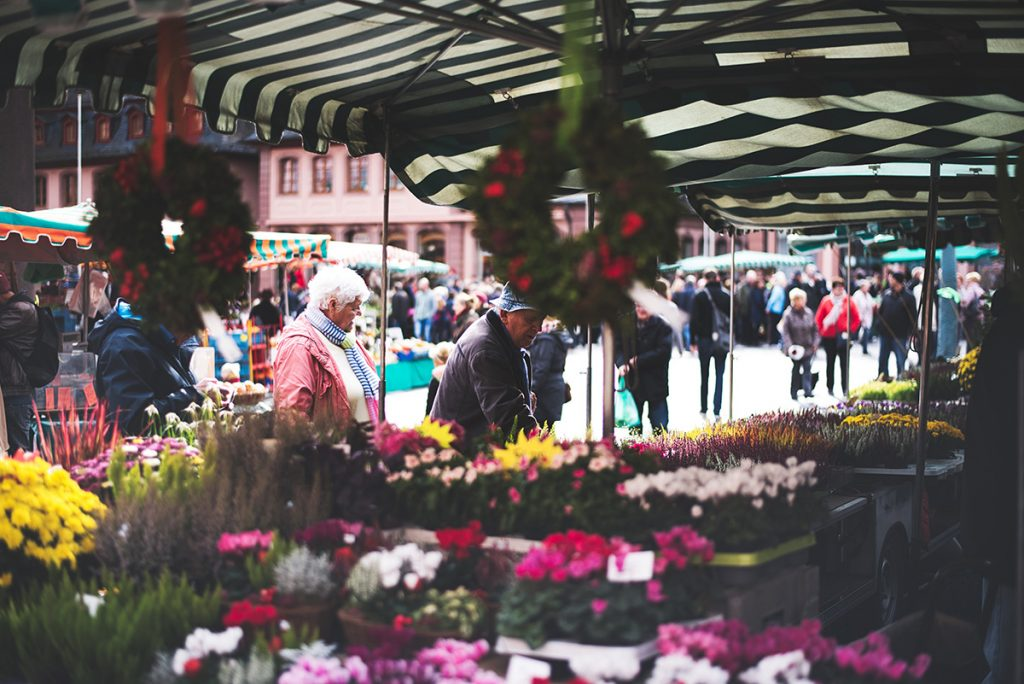 An elderly woman looks at a large collection of flowers under a green and white tent.
