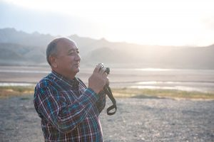 Elderly man taking photos outdoors, with mountains in the background