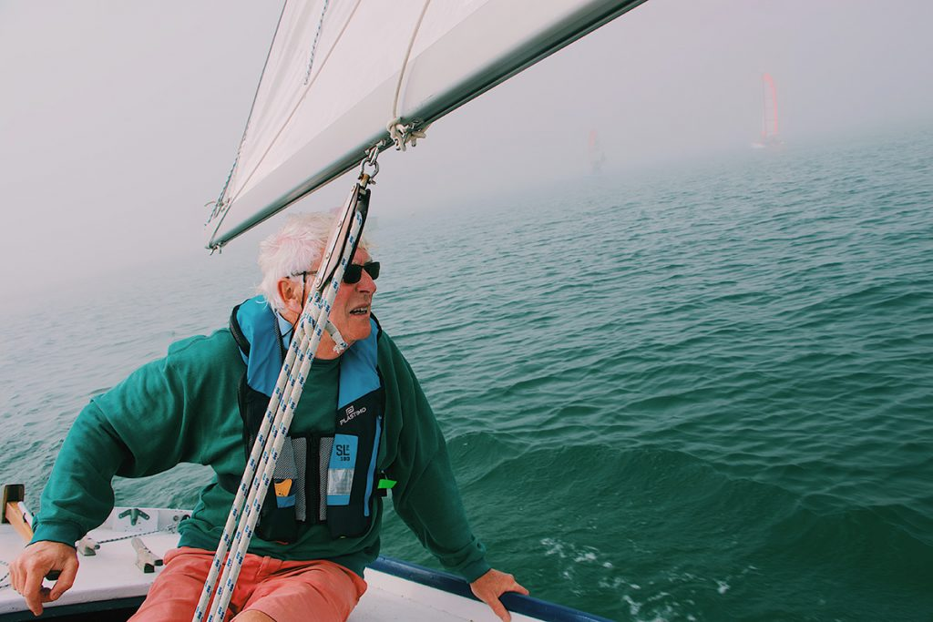 Elderly man in a sailboat on the water