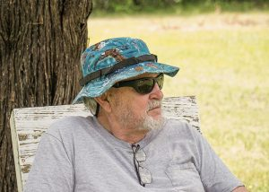 An older man in a hat looks off into the distance outdoors.