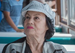 An older woman in a hat looks off into the distance in a diner.